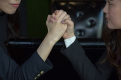 Närbild av en affärskvinnaCompeting In Arm för två asiat brottning royaltyfri foto