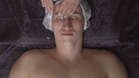 Närbild av en ansikts- massage för stiligt häleri för ung man på brunnsortmitten arkivfilmer