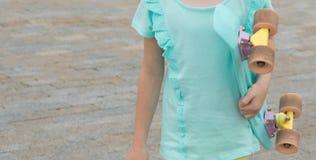 Närbild av en barn-, flicka- och skateboardtorso, mot en bakgrund av stenpavers royaltyfria bilder