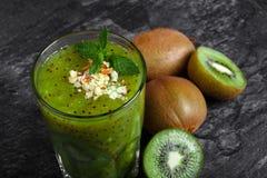Närbild av en blandad kiwismoothie med näringsrika ingredienser på ett mörker - grå bakgrund Healthful exotiska frukter fotografering för bildbyråer