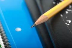 Närbild av en blyertspenna på anteckningsböcker Royaltyfri Bild