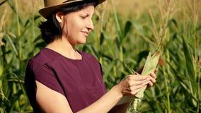 Närbild av en bondekvinna i sugrörhatt mot bakgrunden av ett fält för grön havre på en solig sommardag En bonde arkivfilmer