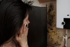 Närbild av en chockad kvinna som ser formen på väggen Arkivbild