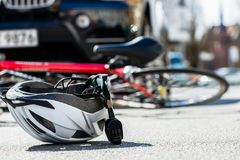 Närbild av en cykla hjälm på asfalten bredvid en cykel Arkivfoto