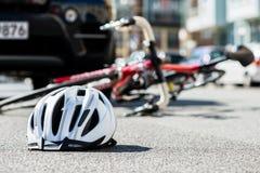 Närbild av en cykla hjälm på asfalten bredvid en cykel Royaltyfri Bild