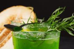 Närbild av en dragondrink Ett exponeringsglas av den gröna alkoholiserade coctailen med en sked Kall växt- drink och melon på en  arkivfoton