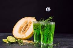 Närbild av en dragondrink Ett exponeringsglas av den gröna alkoholiserade limefruktcoctailen Kall drink och söt snittmelon på en  royaltyfri foto