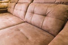 N?rbild av en dyr mjuk textilsoffa av beige f?rg med bruna skuggor f?r lokalsofa f?r bakgrund inre white f?r tappning arkivfoto