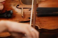 Närbild av en fiol med en pilbåge Brun orkesterfiol Fingrar på fioltangentbordet royaltyfria foton