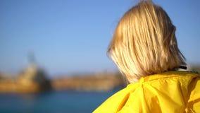 Närbild av en flicka med bärande solglasögon för blont hår och en gul regnrock som står på en klippa i solig blåsväder arkivfilmer