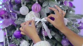 Närbild av en flicka som dekorerar en julgran arkivfilmer