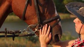 Närbild av en flicka som slår en häst i framsidan lager videofilmer