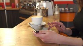 Närbild av en flickas händer med en minnestavla i en coffee shop l?ngsam r?relse lager videofilmer