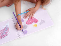 Närbild av en flickateckning Förskole- unge som drar färgrika bilder Ett barn med färgblyertspennor tillbaka begreppsskola till Fotografering för Bildbyråer