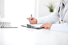 Närbild av en fyllnads- ut ansökningsblankett för kvinnlig doktor, sammanträde på tabellen i sjukhuset royaltyfri foto