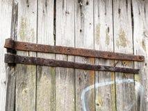 Närbild av en gammal ladugårddörr med rostig metall, laven, mossa och en kant av grafitti Royaltyfri Foto