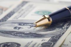 Närbild av en guld och en svart penna på 100 dollarräkningar Arkivbilder