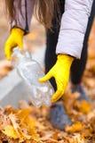 Närbild av en hand för flicka` s i handskar med en plast- flaska royaltyfria foton