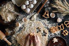 Närbild av en hand för kvinna` s med en deg Kvinnan klipper en kaka med en kakaskärare i formen av lite Royaltyfri Bild