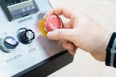 Närbild av en hand för man` s på en röd knapp på kontrollbordet Nöd- stopp eller start av utrustning och produktion arkivfoton