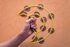 Närbild av en hand för man` som s rymmer en gul tambarine på en apelsin Royaltyfri Bild