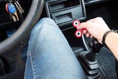 Närbild av en hand för man` som s spelar med en spinnare medan i en trafikstockning på bakgrunden av inre för bil` s Arkivbild