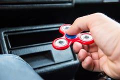 Närbild av en hand för man` som s spelar med en spinnare medan i en trafikstockning på bakgrunden av inre för bil` s Royaltyfri Fotografi