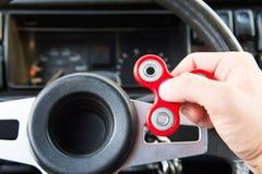 Närbild av en hand för man` som s spelar med en spinnare medan i en trafikstockning på bakgrunden av inre för bil` s Fotografering för Bildbyråer