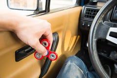 Närbild av en hand för man` som s spelar med en spinnare medan i en trafikstockning på bakgrunden av inre för bil` s Royaltyfria Foton