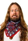 Närbild av en hippieman med ett galet uttryck. Arkivbild