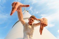 Närbild av en kall tonårs- grabb En stilig man nära den elektriska väderkvarnen En säker man på en bakgrund för blå himmel arkivfoto