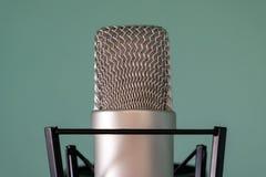 Närbild av en kondensatorstudiomikrofon med en stötdämpare på en blå bakgrund Begreppet av den högkvalitativa professionell fotografering för bildbyråer