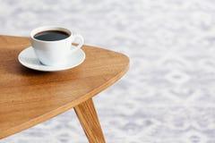 Närbild av en kopp kaffe på en trätabell fotografering för bildbyråer