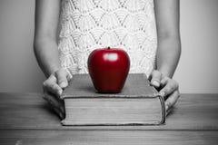 Närbild av en kristen kvinna som läser bibeln med det röda äpplet royaltyfri fotografi
