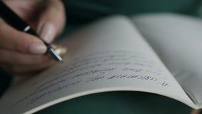 Närbild av en kvinna som skriver en hand på en tom anteckningsbok med en penna stock video