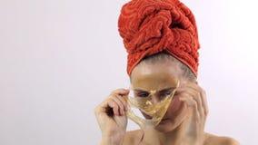 Närbild av en kvinna som tar bort en guld- maskering från hennes framsida arkivfilmer