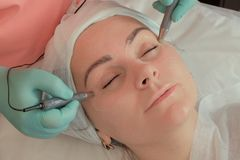 Närbild av en kvinna som tar ett tillvägagångssätt i en skönhetsalong Microcurrent stimulans av huden runt om ögonen moisturizer arkivbild