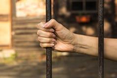 Närbild av en kvinnahand med en järnstång i arrest arkivfoto