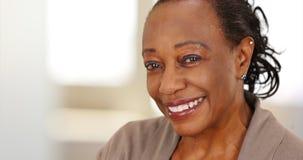 Närbild av en le äldre afrikansk amerikankvinna på arbete royaltyfri fotografi