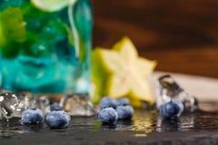Närbild av en ljus uppfriskande blå laguncoctail med blåbär, mintkaramellen och carambolaen på träbakgrunden Arkivfoto