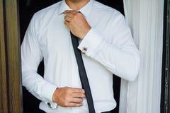 Närbild av en man i en tux som fixar hans tappningcufflink brudgumflugacufflinks royaltyfria bilder