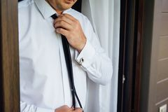 Närbild av en man i en tux som fixar hans tappningcufflink brudgumflugacufflinks royaltyfri bild