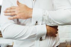 Närbild av en man i en tux som fixar hans tappningcufflink brudgumflugacufflinks arkivfoton