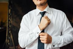 Närbild av en man i en tux som fixar hans tappningcufflink brudgumflugacufflinks arkivfoto