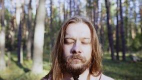 Närbild av en man med det långa hår och skägget Han står i mitt av skogen med hans stängda ögon ?gonblick av koncentration stock video