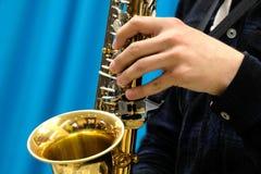 Närbild av en manlig hand som spelar en musiker på en guld- saxofon på en blå bakgrund Tema för musiknyheterna arkivbild