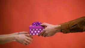 Närbild av en mans hand som framför en kvinnas gåva Begrepp av att fira nytt år och jul Gåva till valentin arkivfilmer