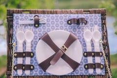 Närbild av en picknickresväskakorg med disk - plattor, skedar och gafflar royaltyfria bilder