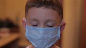Närbild av en pojke som bär en maskering på ett mottagande på doktorn arkivfilmer
