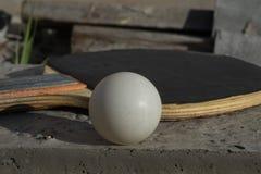Närbild av en racket och en boll för att spela bordtennis med en mjuk bakgrund arkivbild